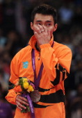 Chong Wei Lee of Malaysia reacts after receiving his Silver medal on the podium following the Men's Singles Badminton Gold Medal match on Day 9 of...