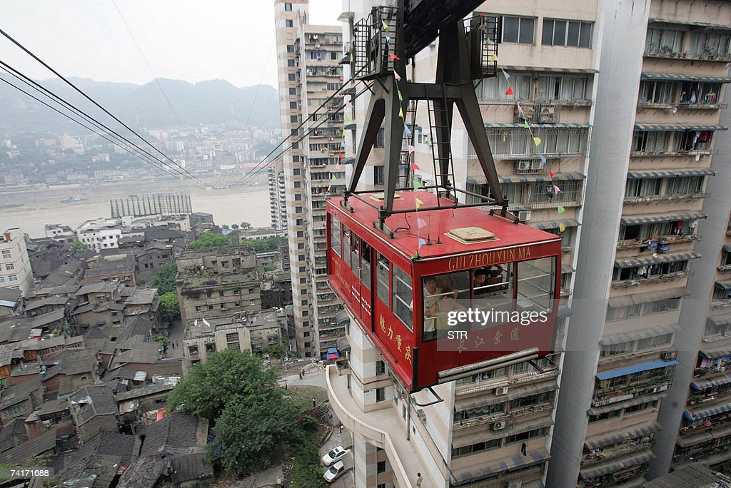 Tourists take a cable car ride across China's mighty Yangtze River enjoying the view of the 3000yearold Chongqing city built on top of steep hills...
