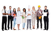 Group of diverse people in different occupations standing close to each other and against white background and smiling