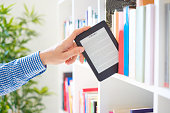 Hands holding ebook on bookshelf background.Copy space on digital tablet display