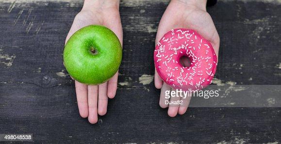 Choosing between apple and doughnut : Stock Photo