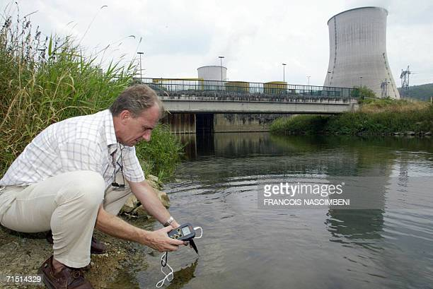 A technician of French electricity group EDF measures the water's temperatures 25 July 2006 near the Chooz nuclear plant northern France A searing...