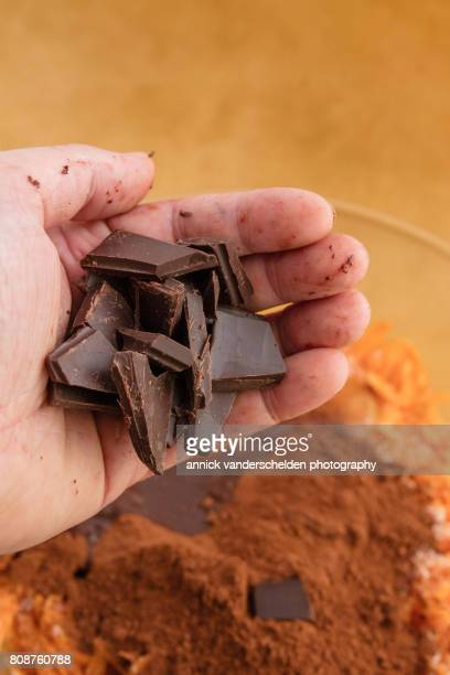Chopped chocolate above a mixing bowl with ingredients to make a brownie of sweet potato.
