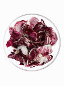 Chopped radicchio in glass bowl on white background, overhead view