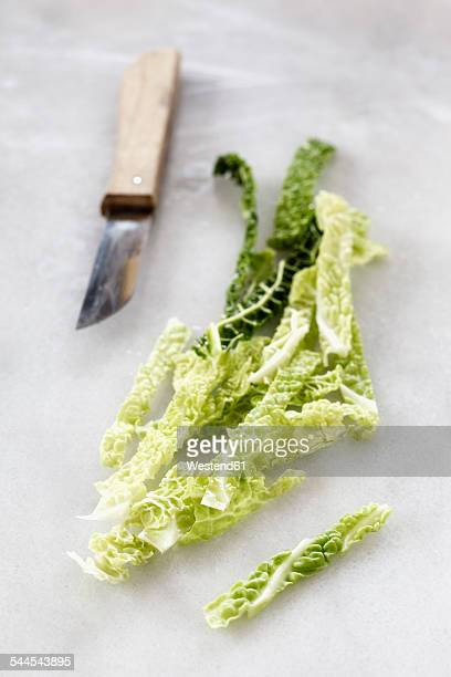Chopped savoy and a kitchen knife on white marble