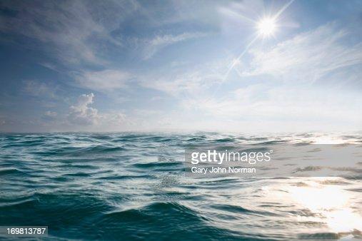 choppy blue sea with blue sky and sun
