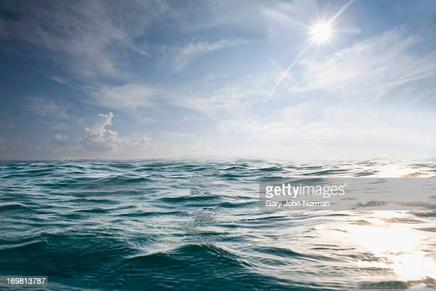 choppy blue sea with blue sky and sun