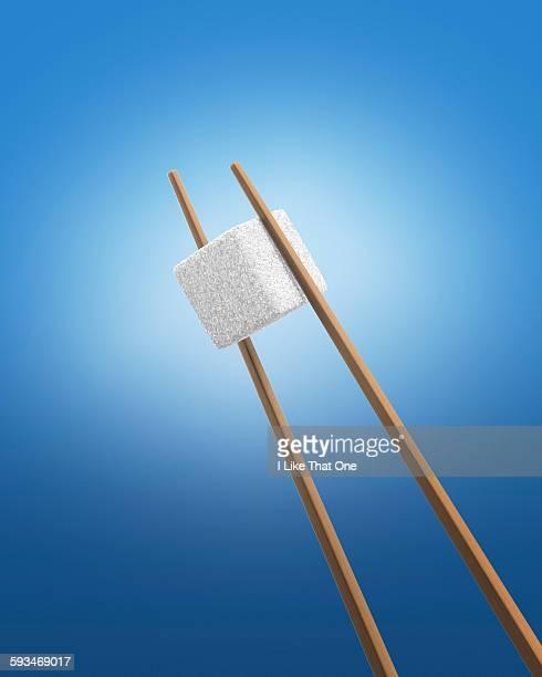 Chopsticks holding a white sugar cube