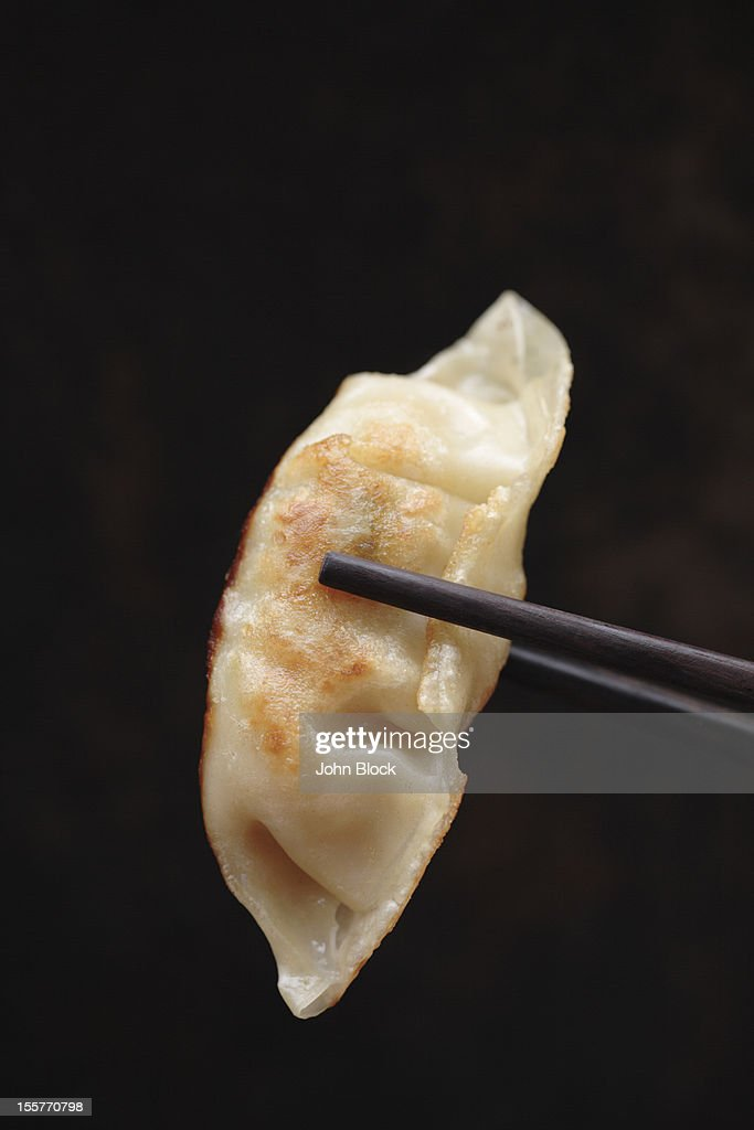 Chopsticks holding Asian dumpling : Stock Photo