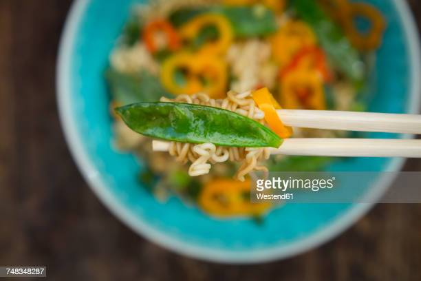 Chopsticks with mie noodles, chili pod and snow pea, close-up