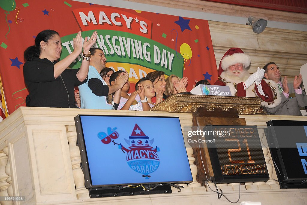 PS 22 choral director Gregg Breinber (3rd-L), Executive Producer of Macy's Thanksgiving Day Parade, Amy Kule (C) and Santa Claus ring the opening bell at the New York Stock Exchange on November 21, 2012 in New York City.