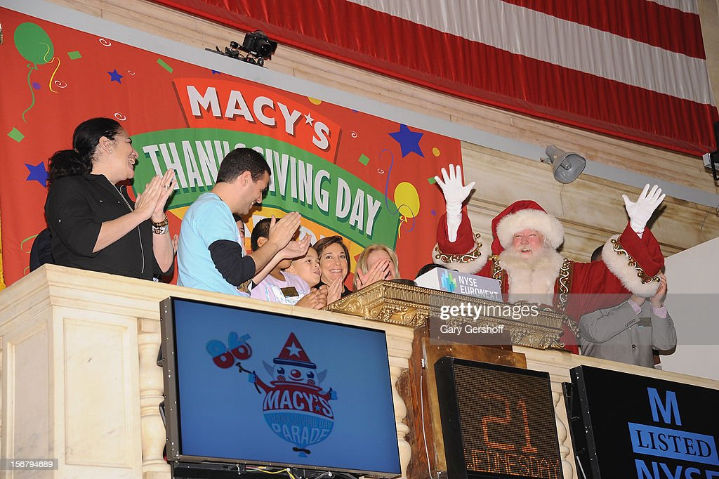 PS 22 choral director Gregg Breinberg (3rd-L), Executive Producer of Macy's Thanksgiving Day Parade, Amy Kule (C) and Santa Claus ring the opening bell at the New York Stock Exchange on November 21, 2012 in New York City.