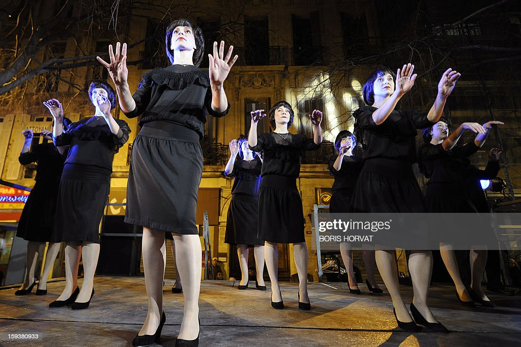 Choristers looking alike French singer Mireille Mathieu, whose group is named 'les Mireille', sing in front of the Theatre du Gymnase, on January 12, 2013 at the Vieux-Port harbour in Marseille, southern France, as part of the opening festivities marking Marseille as the 2013 European Capital of Culture.