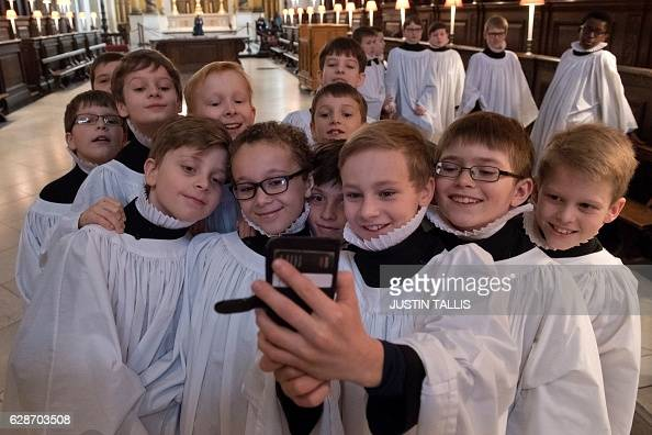 TOPSHOT Choristers of St Paul's Cathedral take a 'selfie' photograph after rehearsing in the inside the cathedral in central London on December 9...