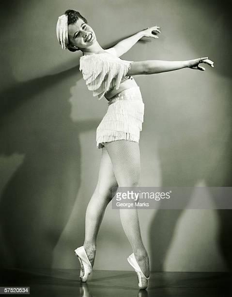 Chorus girl dancing in studio, (B&W)