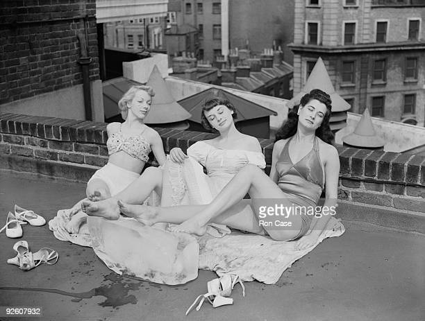 Chorus girls from the show 'Sauce Tartare' at the Cambridge Theatre in London relax on the roof of the theatre 28th June 1949 From left to right they...