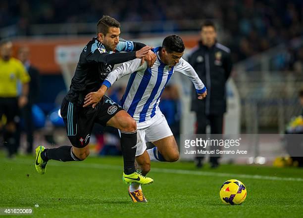 Chory Castro of Real Sociedad competes for the ball with Hugo Mallo of Celta de Vigo during the La Liga match between Real Sociedad de Futbol and...