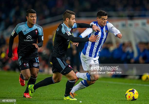 Chory Castro of Real Sociedad competes for the ball with Hugo Mallo and Rafinha of Celta de Vigo during the La Liga match between Real Sociedad de...