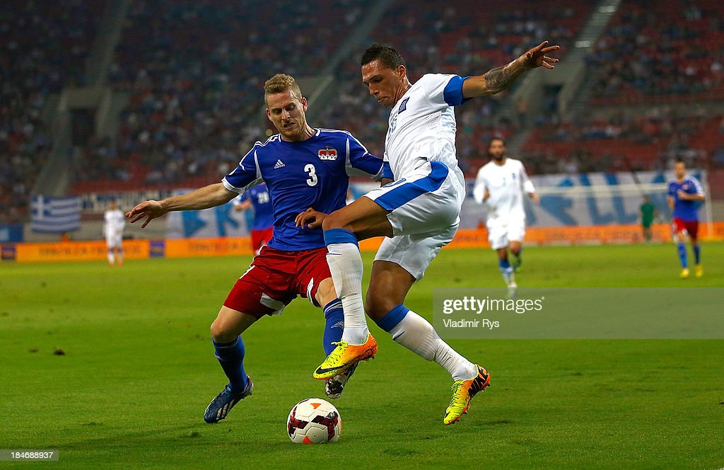 Chose Cholebas of Greece (R) and Yves Oehri of Liechtenstein battle for the ball during the group G FIFA 2014 World Cup Qualifier match between Greece and Liechtenstein at Karaiskakis Stadium on October 15, 2013 in Athens, Greece.