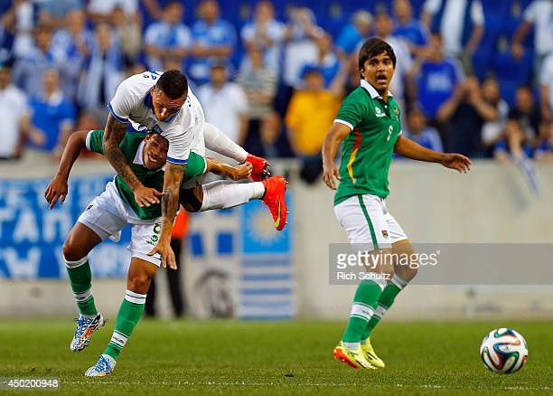 Chose Loint Cholevas of Greece gets flipped by Diego Bejarano of Bolivia after attempting a header as Marcelo Martins Moreno of Bolivia looks on...