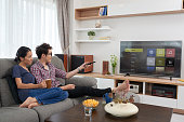 Asian couple choosing channel on their smart tv
