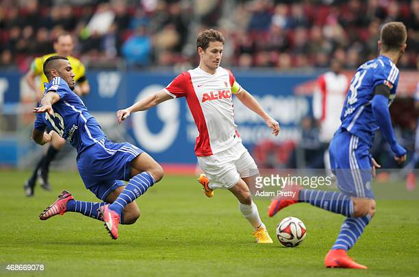 E ChoupoMoting of FC Schalke challenges Paul Vergaegh of FC Augsburg during the Bundesliga match between FC Augsburg and FC Schalke 04 at SGL Arena...