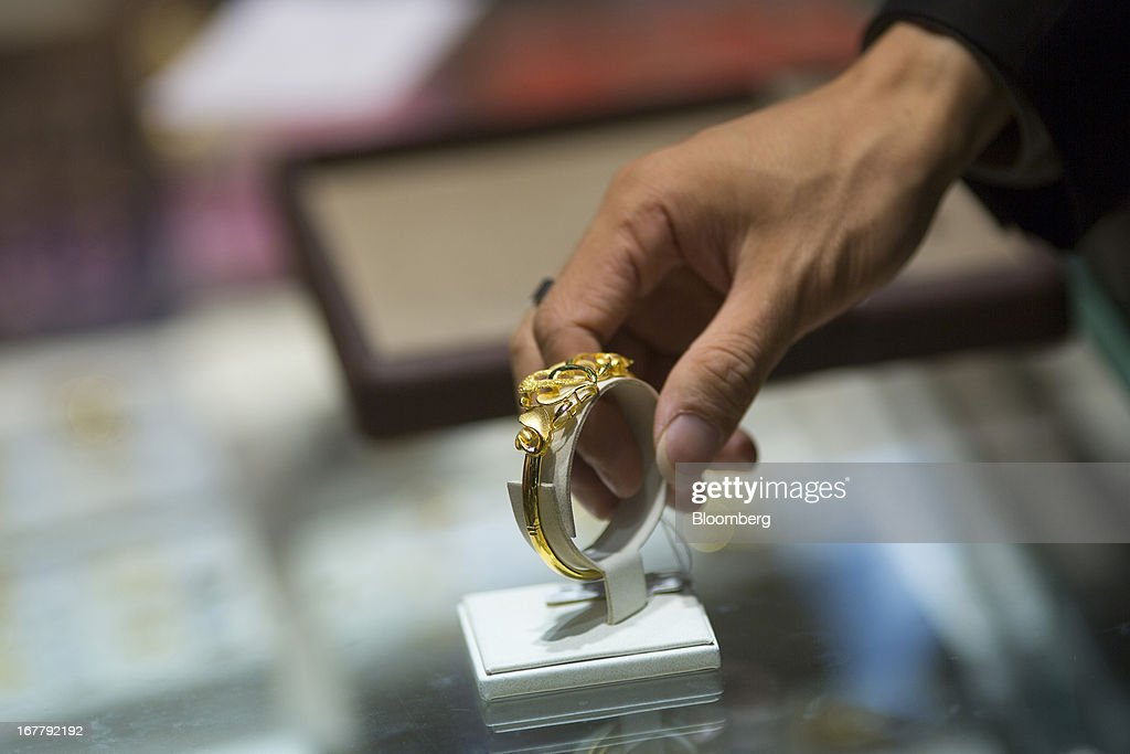 A Chow Sang Sang Holdings International Ltd. employee holds a gold bracelet at the company's jewelry store in the Mongkok district of Hong Kong, China, on Tuesday, April 30, 2013. Chow Sang Sang said that jewelry sales at its 44 shops in Hong Kong more than doubled in the two weeks ended April 27 from a year ago. Photographer: Lam Yik Fei/Bloomberg via Getty Images