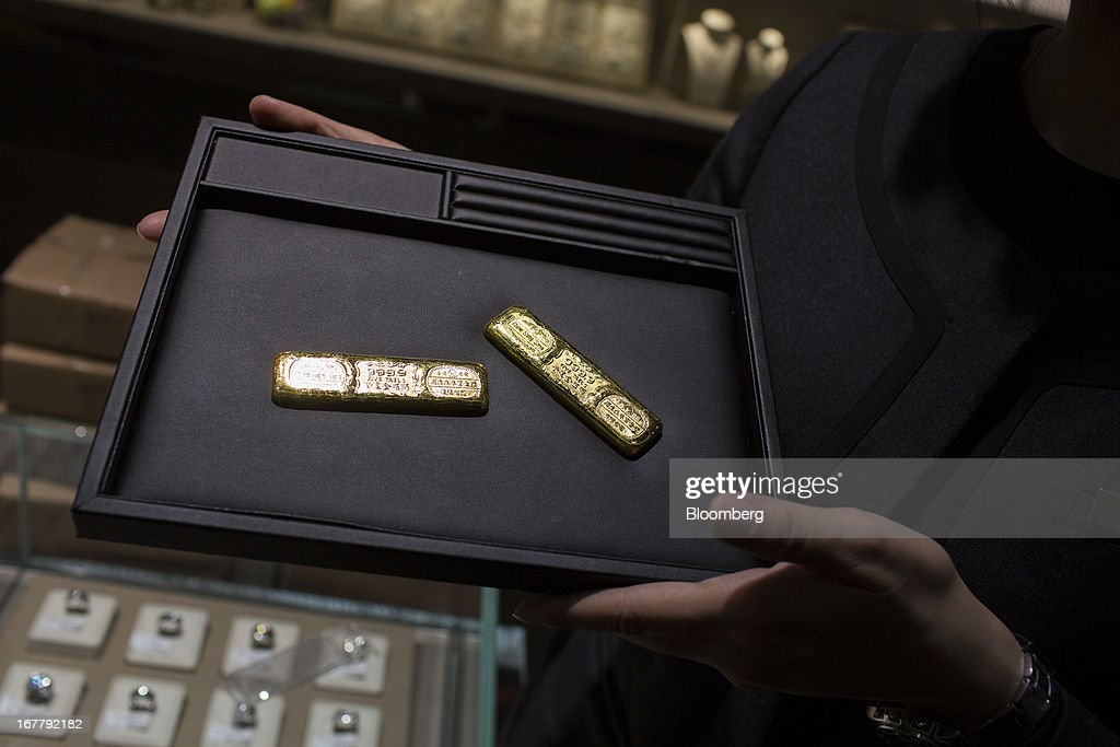 A Chow Sang Sang Holdings International Ltd. employee holds a pair of gold bars each weighing five taels (187 grams) for a photograph at a Chow Sang Sang Holdings International Ltd. jewelry store in the Mongkok district of Hong Kong, China, on Tuesday, April 30, 2013. Chow Sang Sang said that jewelry sales at its 44 shops in Hong Kong more than doubled in the two weeks ended April 27 from a year ago. Photographer: Lam Yik Fei/Bloomberg via Getty Images