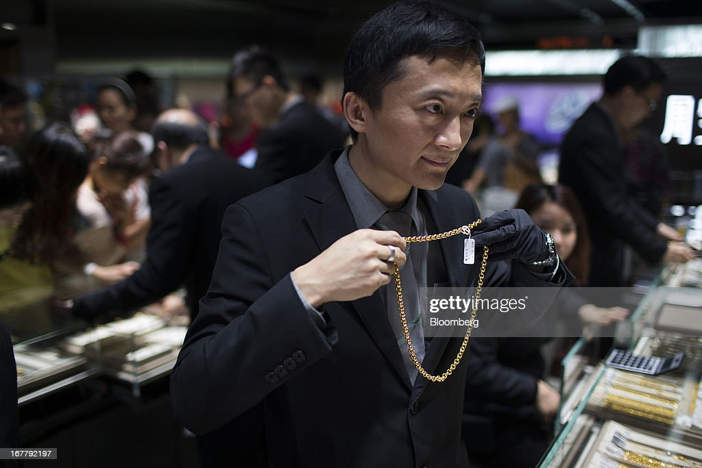 A Chow Sang Sang Holdings International Ltd. employee shows a gold chain to customers at the company's jewelry store in the Mongkok district of Hong Kong, China, on Tuesday, April 30, 2013. Chow Sang Sang said that jewelry sales at its 44 shops in Hong Kong more than doubled in the two weeks ended April 27 from a year ago. Photographer: Lam Yik Fei/Bloomberg via Getty Images