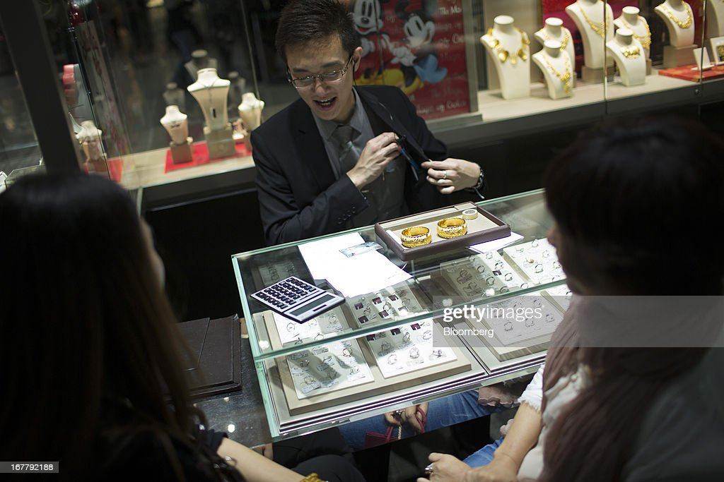 A Chow Sang Sang Holdings International Ltd. employee shows gold bangles to customers at the company's jewelry store in the Mongkok district of Hong Kong, China, on Tuesday, April 30, 2013. Chow Sang Sang said that jewelry sales at its 44 shops in Hong Kong more than doubled in the two weeks ended April 27 from a year ago. Photographer: Lam Yik Fei/Bloomberg via Getty Images