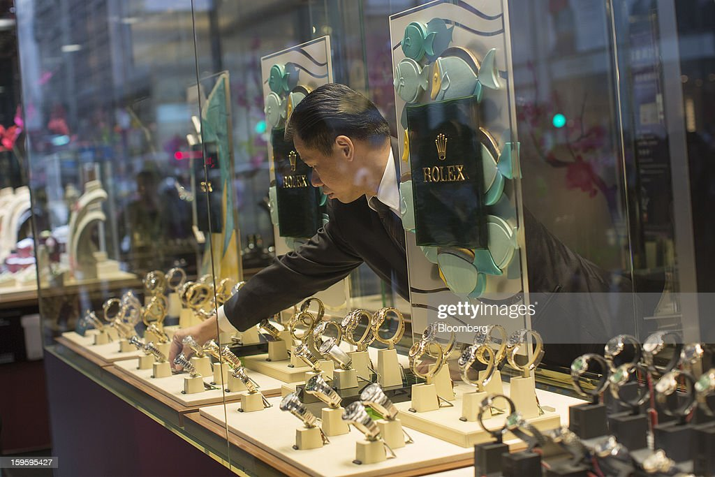 A Chow Tai Fook Jewellery Group Ltd. employee arranges Rolex Group watches displayed in the window of the company's store in the Central district of Hong Kong, China, on Wednesday, Jan. 16, 2013. Chow Tai Fook Jewellery, the world's biggest jeweler by market value, posted an 8 percent drop in third-quarter same-store sales as Chinese shoppers curbed spending amid a slower economy. Photographer: Jerome Favre/Bloomberg via Getty Images