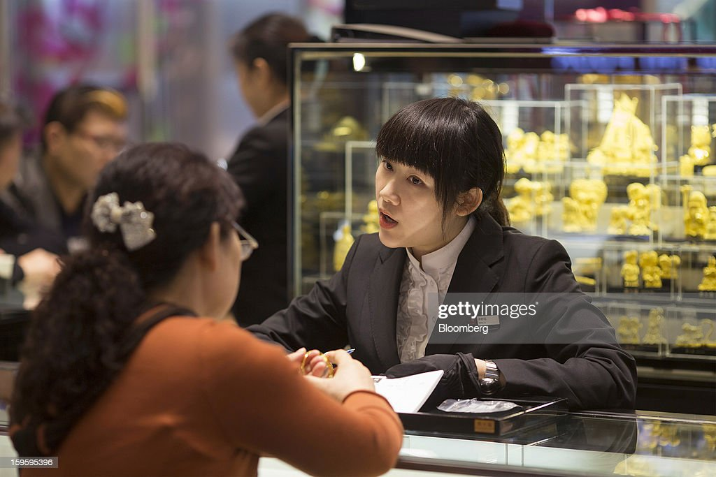 A Chow Tai Fook Jewellery Group Ltd. employee attends to a customer in the company's store in the Central district of Hong Kong, China, on Wednesday, Jan. 16, 2013. Chow Tai Fook Jewellery, the world's biggest jeweler by market value, posted an 8 percent drop in third-quarter same-store sales as Chinese shoppers curbed spending amid a slower economy. Photographer: Jerome Favre/Bloomberg via Getty Images