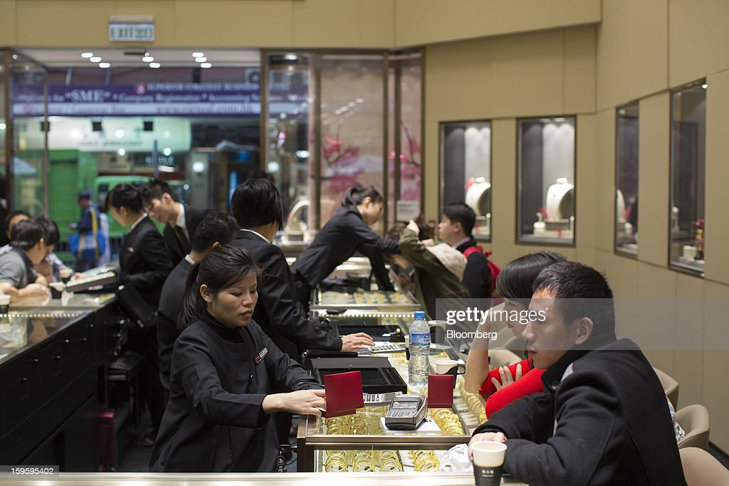 Chow Tai Fook Jewellery Group Ltd. employees attend to customers in the company's store in the Central district of Hong Kong, China, on Wednesday, Jan. 16, 2013. Chow Tai Fook Jewellery, the world's biggest jeweler by market value, posted an 8 percent drop in third-quarter same-store sales as Chinese shoppers curbed spending amid a slower economy. Photographer: Jerome Favre/Bloomberg via Getty Images