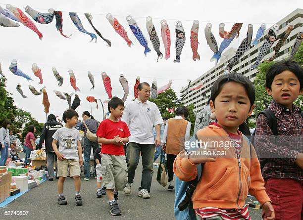 Chrildren walk under fluttering carp streamers at a free market in a park in Tokyo 01 May 2005 as part of an annual event for Japan's national...