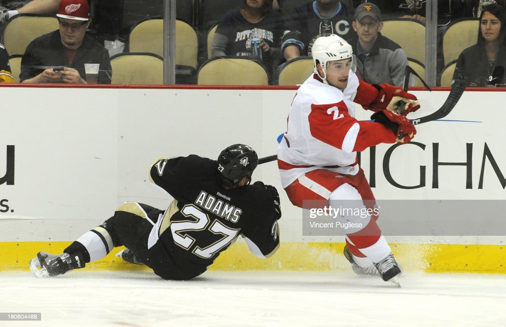 Chris Adams # 27 of the Pittsburgh Penguins challenges Brendan Smith # 2 of the Detroit Red Wings during the third period of a preseason game on September 16, 2013 at the CONSOL Energy Center in Pittsburgh, Pennsylvania.