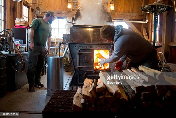 Chris and Jason Grossman load wood into a wood burner while boiling maple sap in the evaporator in their sugar shack at Grossman Brothers Maple...