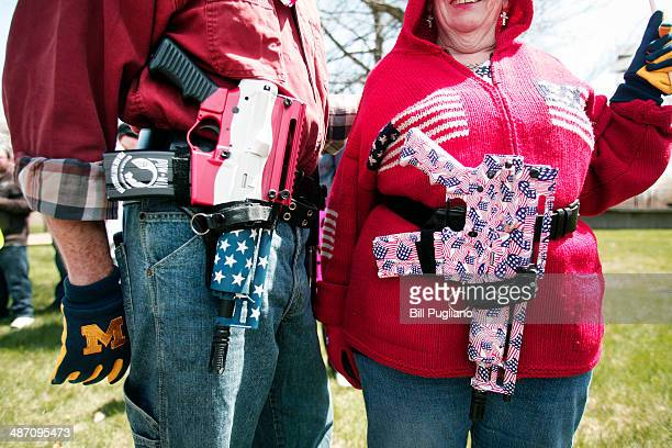 Chris and Marty Welch of Cadillac Michigan carry decorated Olympic Arms 223 pistols at a rally for supporters of Michigan's Open Carry law April 27...