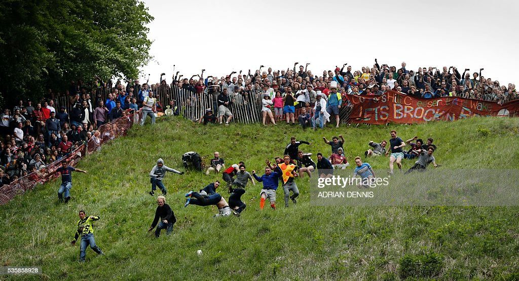 Chris Andersen (Below L) gets ahead of his fellow competitors as they tumble down Cooper's Hill in pursuit of a round Double Gloucester cheese during the annual Cooper's Hill cheese rolling competition near the village of Brockworth, Gloucester, in western England, on May 30, 2016. Anderson went on to win two out of the four races taking his total to 15 cheeses over the years. The annual Cooper's Hill Cheese Rolling involves hordes of fearless competitors chasing an eight pound Double Gloucester cheese down a steep hill. The slope has a gradient in places of 1-in-2 and in others 1-in-1, its surface is very rough and uneven and it is almost impossible to remain on foot for the descent. The winner of the downhill race wins the cheese. / AFP / ADRIAN