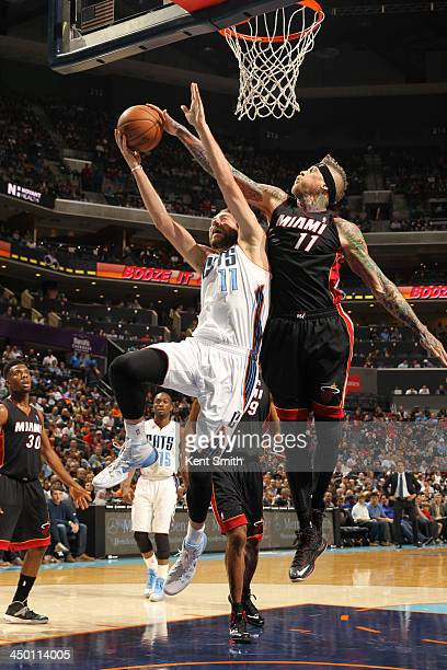 Chris Andersen of the Miami Heat blocks a shot against Josh McRoberts of the Charlotte Bobcats during the game at the Time Warner Cable Arena on...