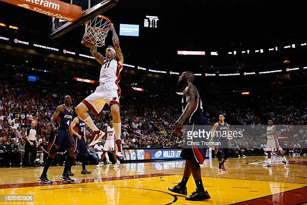 Chris Andersen of the Miami Heat dunks the ball as Anthony Tolliver and Ivan Johnson of the Atlanta Hawks look on at American Airlines Arena on March...