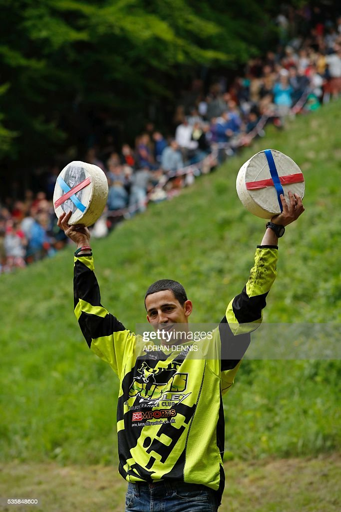 Chris Anderson poses for pictures with his prize cheeses after winning his second race during the annual Cooper's Hill cheese rolling competition near the village of Brockworth, Gloucester, in western England, on May 30, 2016. The annual Cooper's Hill Cheese Rolling involves hordes of fearless competitors chasing an eight pound Double Gloucester cheese down a steep hill. The slope has a gradient in places of 1-in-2 and in others 1-in-1, its surface is very rough and uneven and it is almost impossible to remain on foot for the descent. The winner of the downhill race wins the cheese. / AFP / ADRIAN
