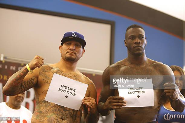 Chris Arreola and WBC World Heavyweight Champion Deontay Wilder pose with 'His Life Matters' signs during their weighin at Legacy Arena at the BJCC...