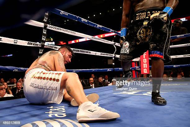 Chris Arreola sits on the canvas after being knocked down for the first time in the sixth round by Bermane Stiverne in their WBC Heavyweight...