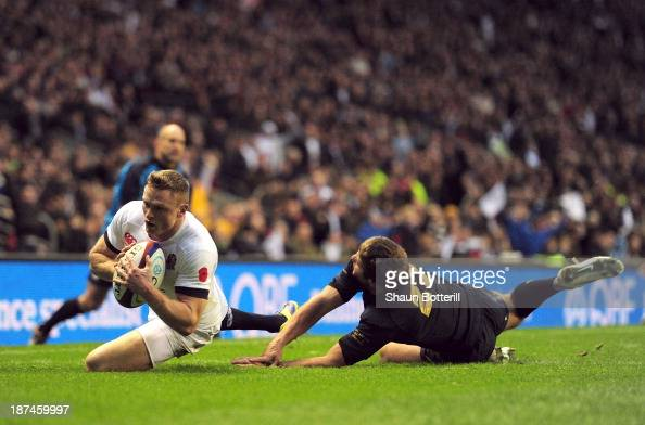 Chris Ashton of England beats the tackle of Santiago Cordero of Argentina to score a try during the QBE International match between England and...