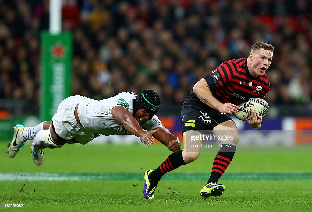Chris Ashton (R) of Saracens beats the tackle of Thierry Dusautoir of Toulouse during the Heineken Cup Pool 3 match between Saracens and Toulouse at Wembley Stadium on October 18, 2013 in London, England.