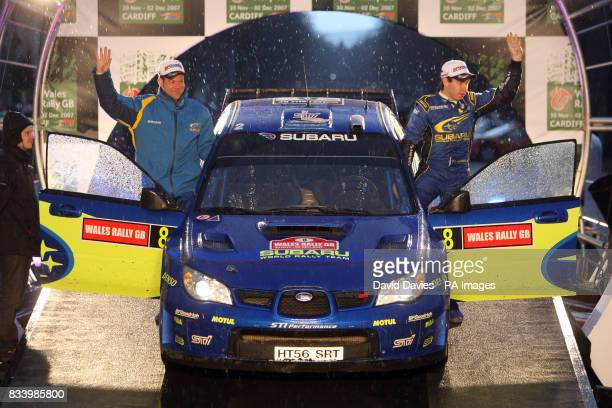 Chris Atkinson of Australia and his co driver Stephane Prevot acknowledge the crowd after finishing seventh in the Subaru Impreza WRC in the Wales...
