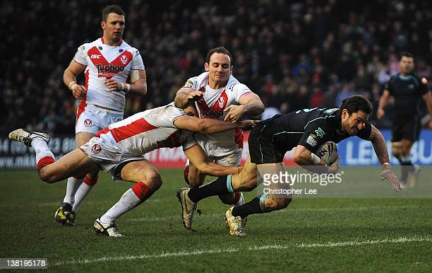 Chris Bailey of Broncos scores a try after getting away from Jon Wilkin and Lance Hohaia of St Helens during the Stobart Super League match between...