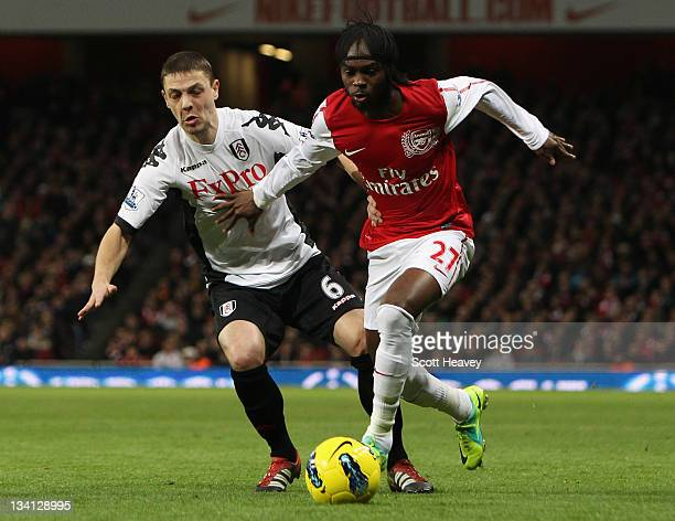 Chris Baird of Fulham and Gervinho of Arsenal battle for the ball during the Barclays Premier League match between Arsenal and Fulham at Emirates...