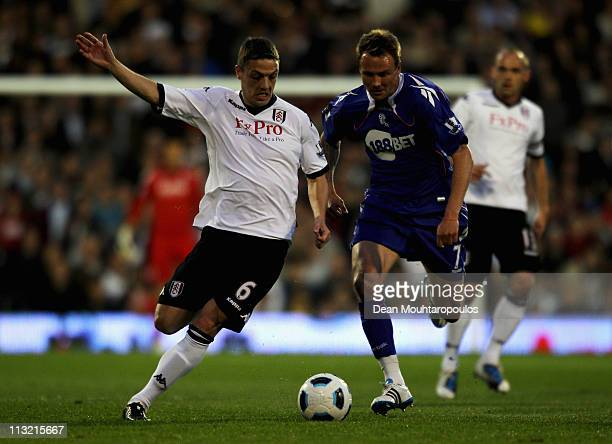 Chris Baird of Fulham battles with Matt Taylor of Bolton during the Barclays Premier League match between Fulham and Bolton Wanderers at Craven...