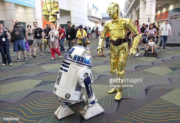 Chris Bartlett of Wake Forest NC dressed as C3PO follows R2D2 Thursday August 12 at the opening day of the Star Wars Celebration V in Orlando Florida